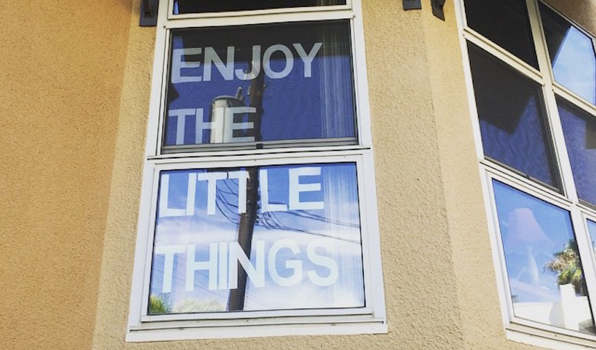 'Enjoy the little things' displayed on a window