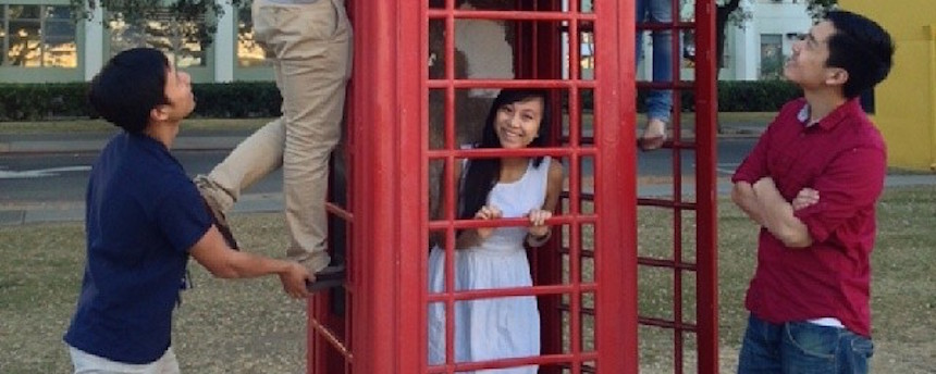 Students posing around a red telephone booth
