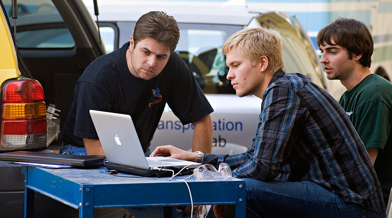 Three men hover over a computer with a car in the background
