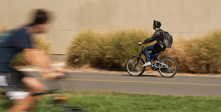 A bicyclist riding fast along a path