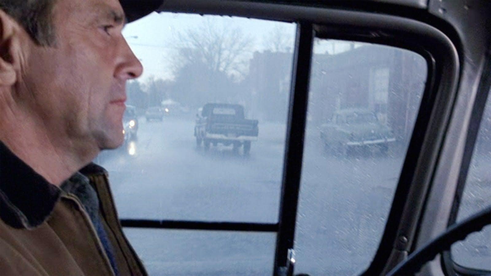 Man in hat sitting in a pickup truck