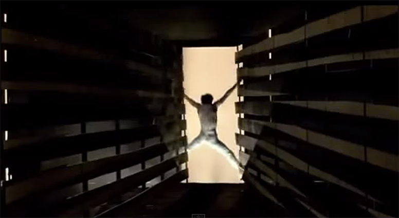 A man leaping out from a long hallway in a warehouse