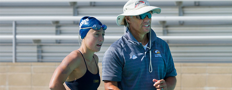 Swim coach Pete Motekaitis talks with a female swimmer at a pool