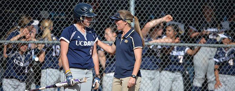 A softball coach, right, talking to a batter in a helmet