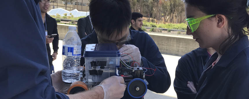 Two students closely examine wires around a miniature car
