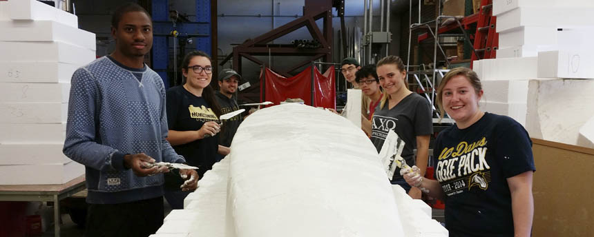 A group of students apply concrete to a canoe mold