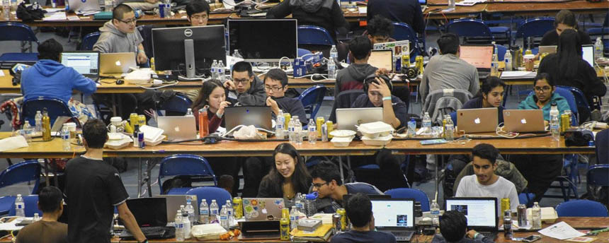 Students crowd tables to work together at computer stations
