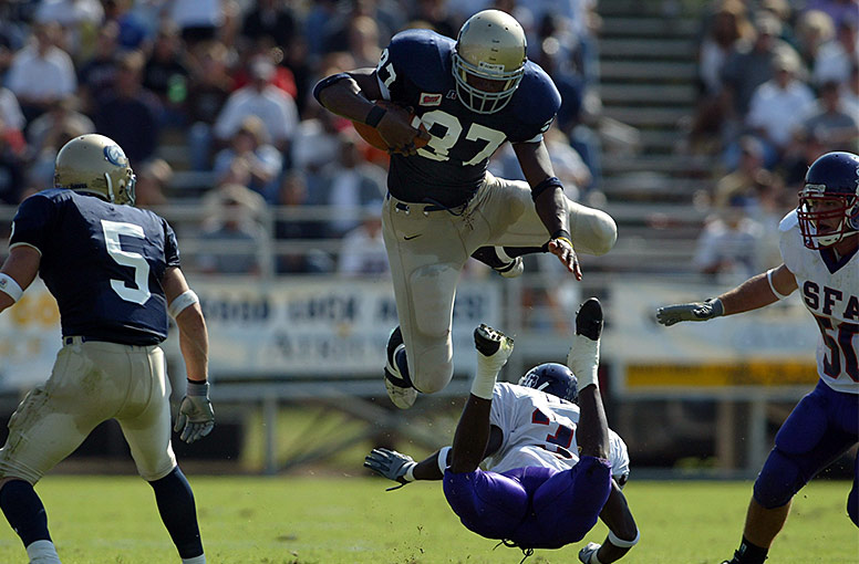 Football player Daniel Fells leaping over a player