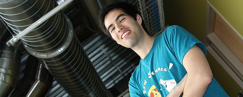 Male student with a food science T-shirt standing in an industrial-looking building