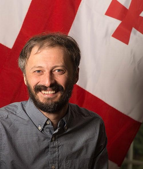 Kakhaber Bakhtadze portrait in front of the Georgian flag