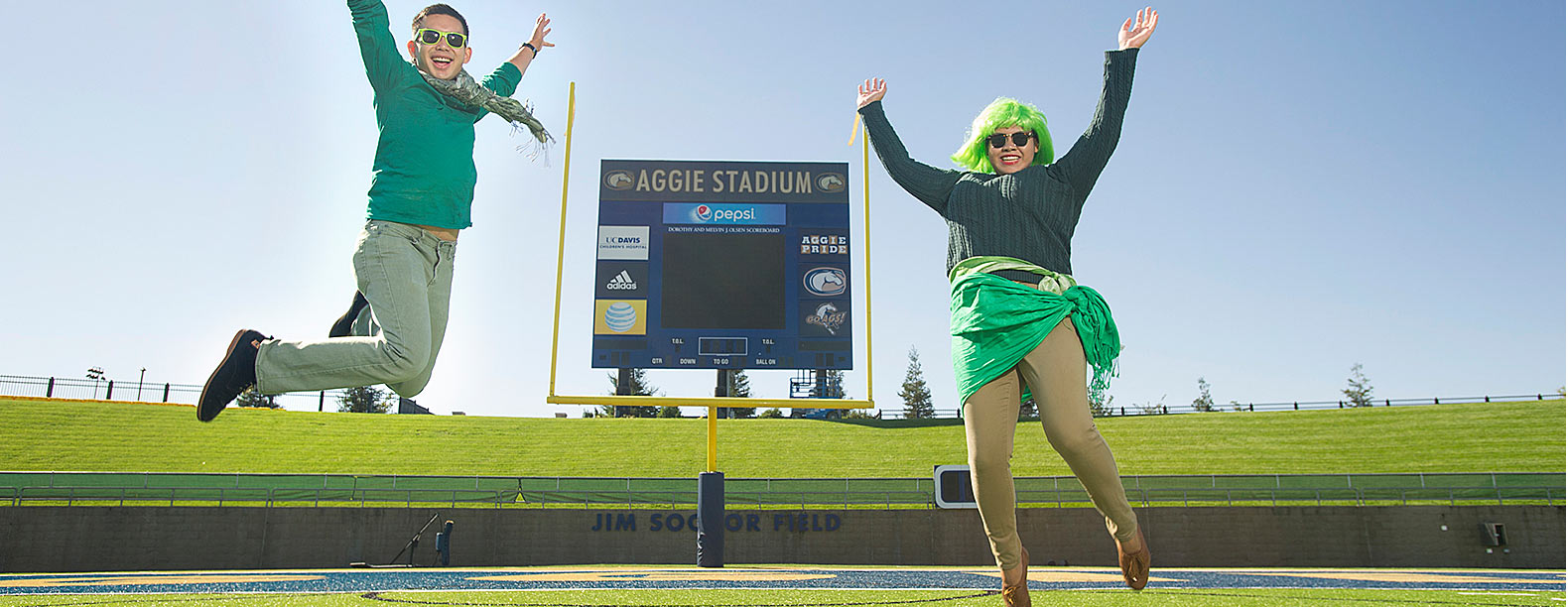 A woman and a man dressed in several pieces of green clothing pose in front of the Aggie Stadium scoreboard