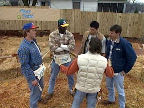 A circle of men in construction clothes in a back yard