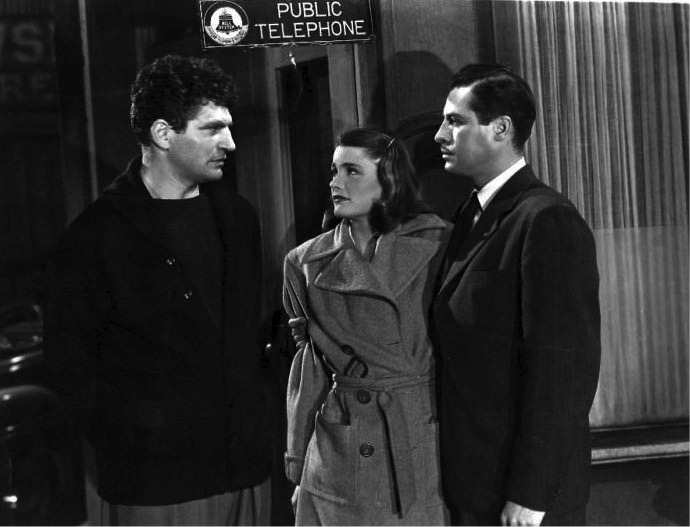 Old noir-style movie set in black and white with two men and a woman talking