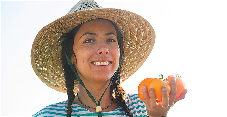 Young woman in a straw hat holding a big tomato