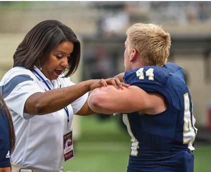 Woman conducting a balance test with a football player