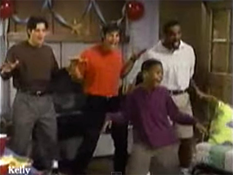 Young boy dancing in front of adult males