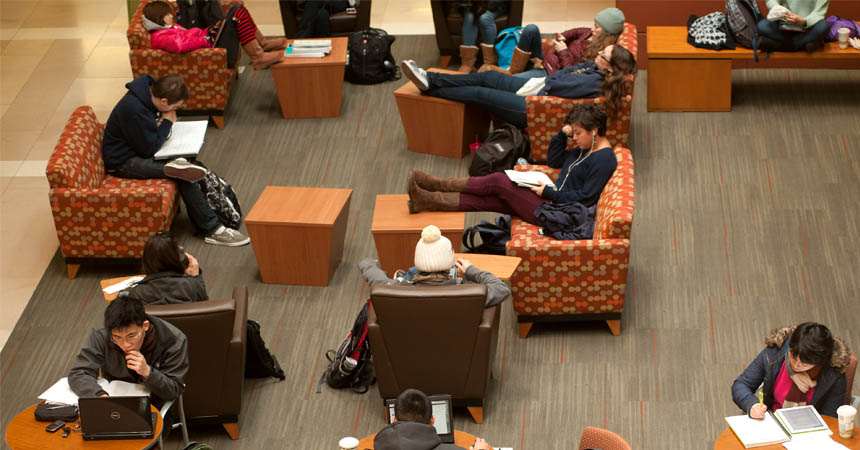 Students occupy tables and couches in building's lobby