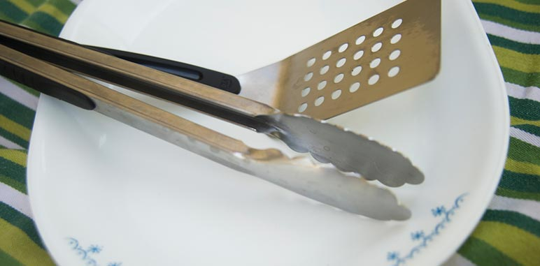 cooking tongs and spatula on a platter