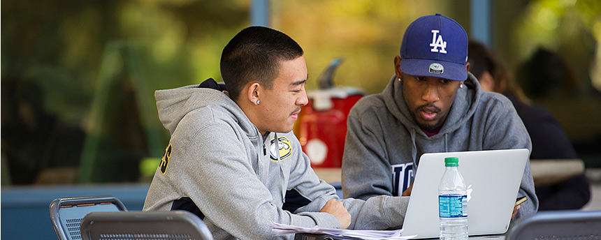 Two male students looking at a computer screen and talking