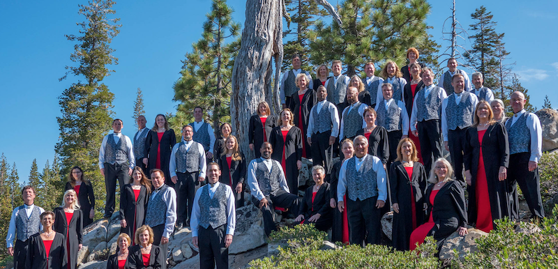 The Sacramento Master Singers standing outdoors on a hill in front of a tree.