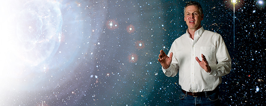 Photo illustration with a man standing and talking in front of a photo of the cosmos
