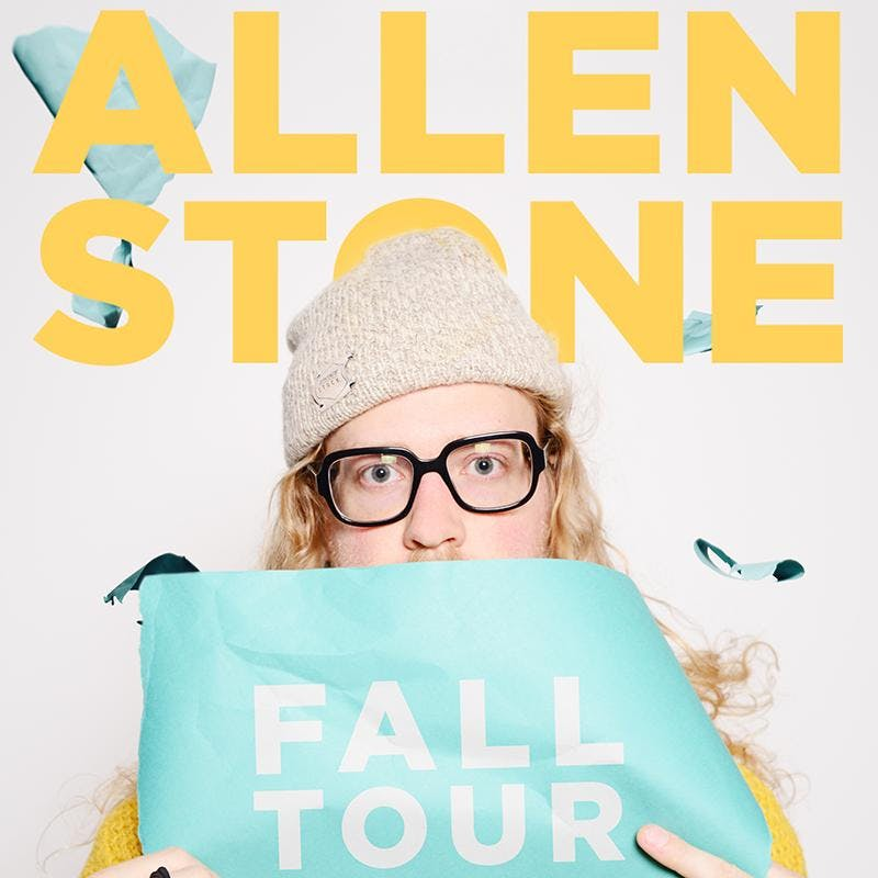 """Allen Stone wearing a wool cap and black-framed glasses, holding up a aqua-marine sheet that says """"Fall Tour."""""""