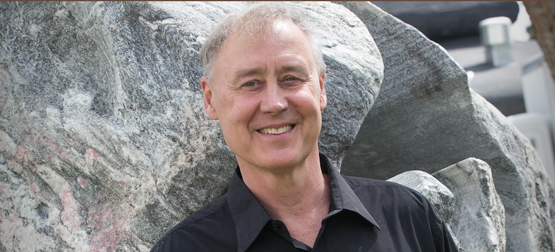 Bruce Hornsby outside standing in front of large rocks.