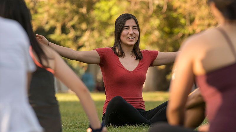 A woman leads an outdoor yoga class