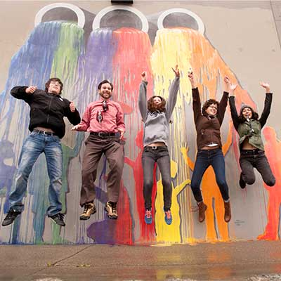 Several people jumping up in front of a colorful mural of paint flowing down