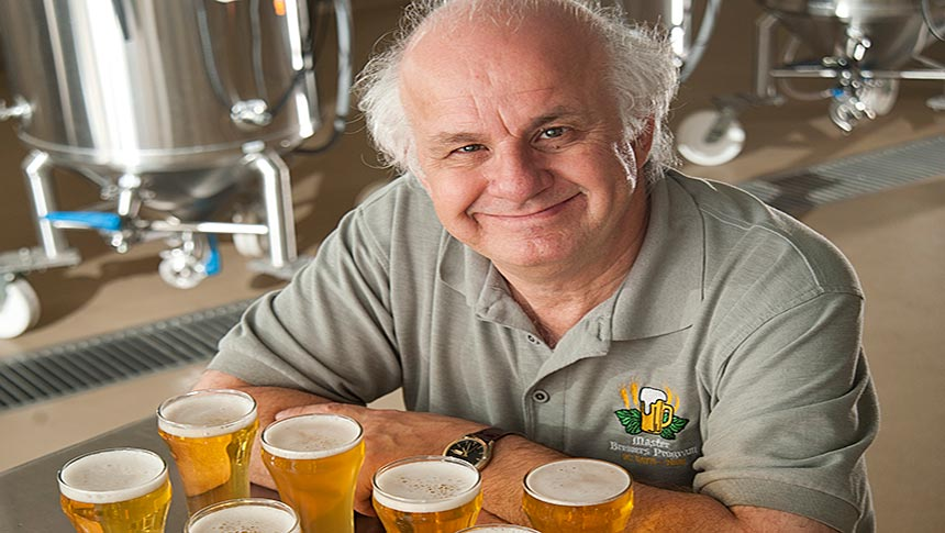 Man sits with arms crossed behind row of full beer glasses