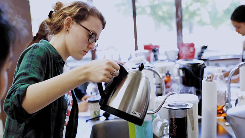 Woman in lab pours coffee from metal pot