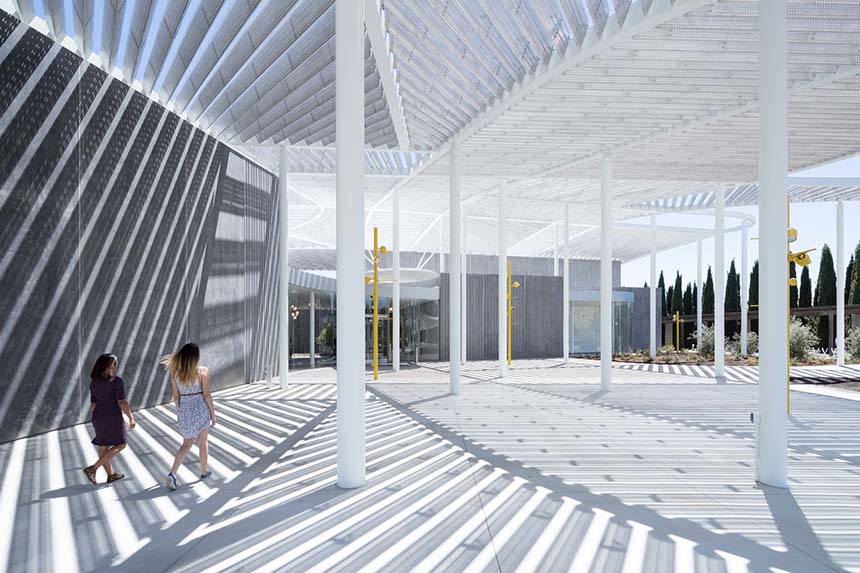 Two women walk under the canopy of the Shrem Museum