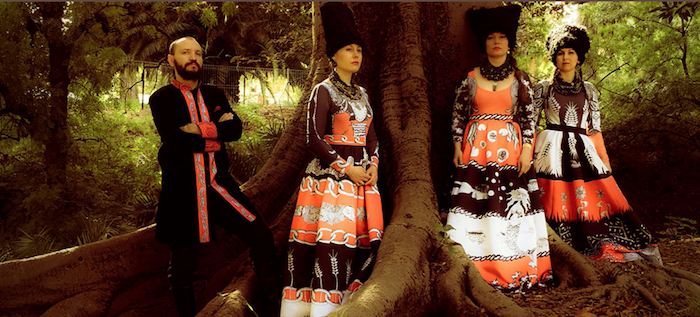 A photo of the band members standing in a forest and wearing colorful Ukrainian garb.