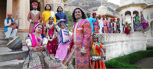 The band members standing in front of an Indian builing, wearing brightly colored costumes.