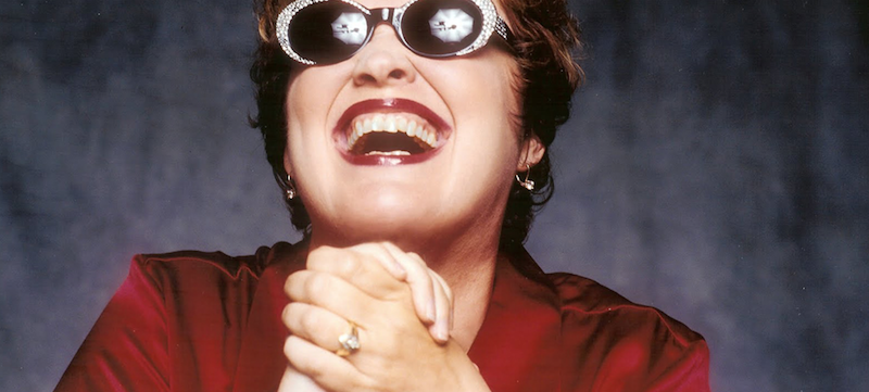 Diane Schuur smiling, wearing sunglasses, with lights relfected in the sunglasses' lenses.