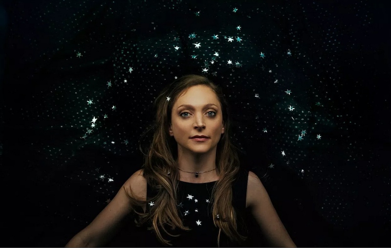 A portrait of Eilen Jewell in front of a black background with diamons-like jewels on it.