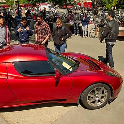 Several men inspecting a Tesla roadster