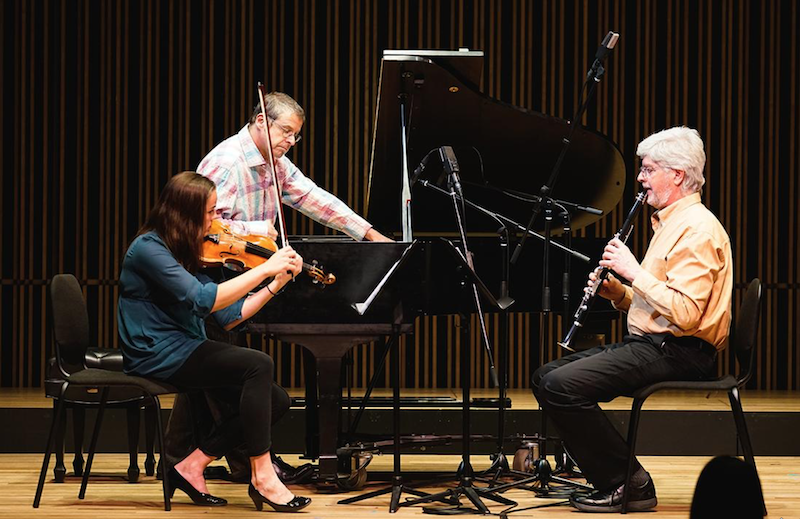 Three members of the ensemble performing on stage.