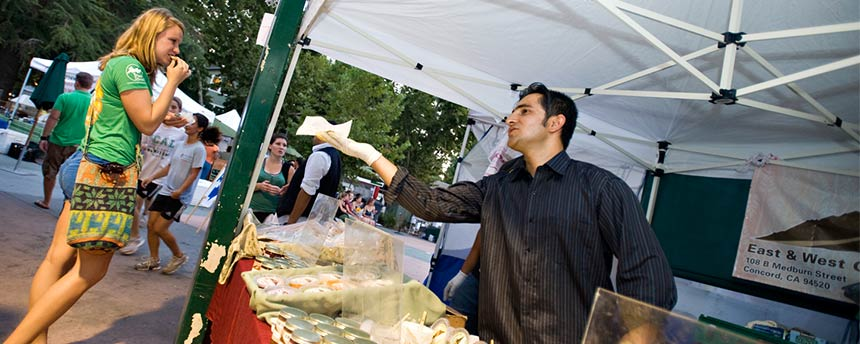 Male vendor handing a sample to a young woman at the Davis Farmers Market