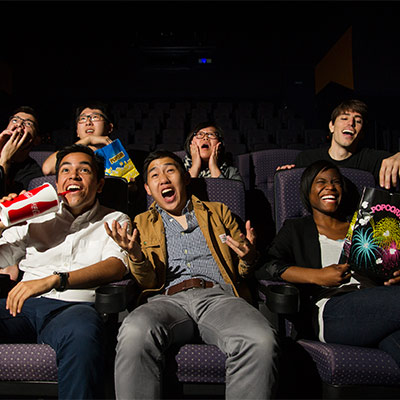 Film audience laughing and eating popcorn