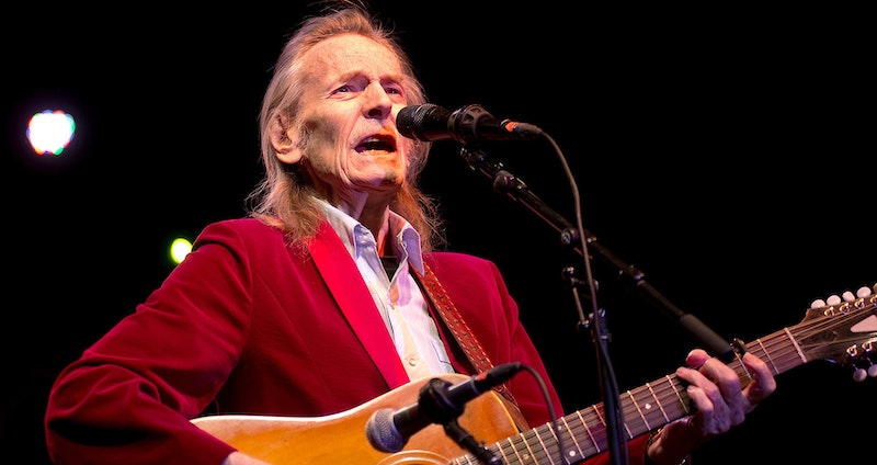 Gordon Lightfoot singing on stage and playing guitar.