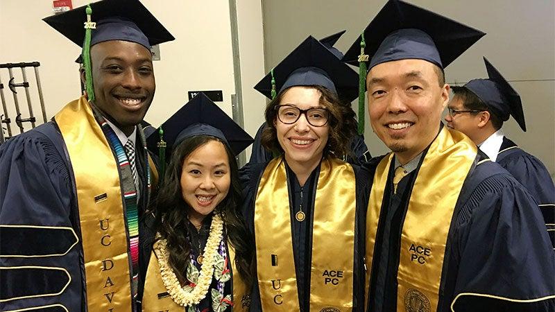 Four graduates pose at School fo medicine commencement