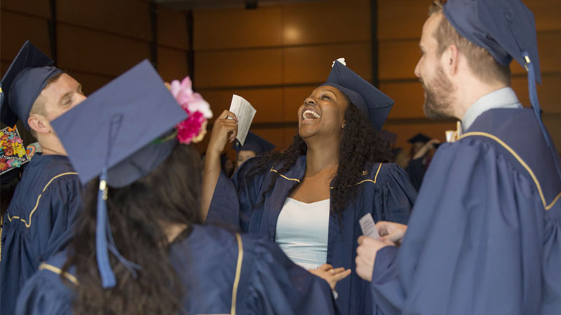 A cluster of graduates laughing
