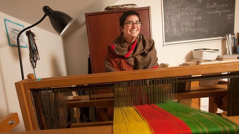 A woman sits at a loom