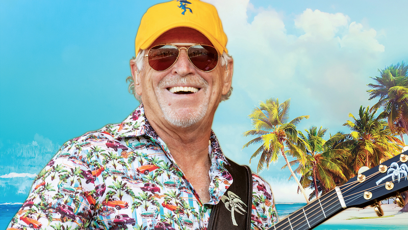 Jimmy Buffett smiling, holding his guitar, wearing sunglasses and a yellow baseball cap.