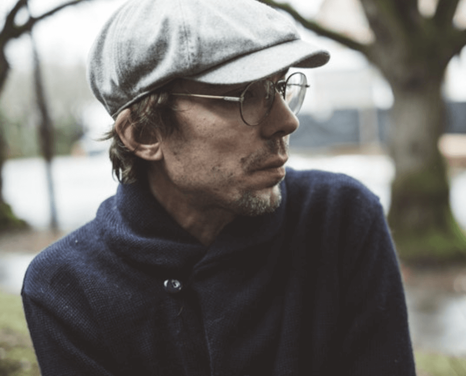 Justin Townes Earle wearing a cap and round-rimmed glasses.