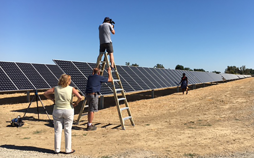 A cameraman stands on a ladder at a solar farm