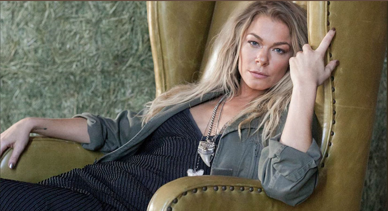 LeeAnn Rimes leaning back on a chair and staring into the camera.