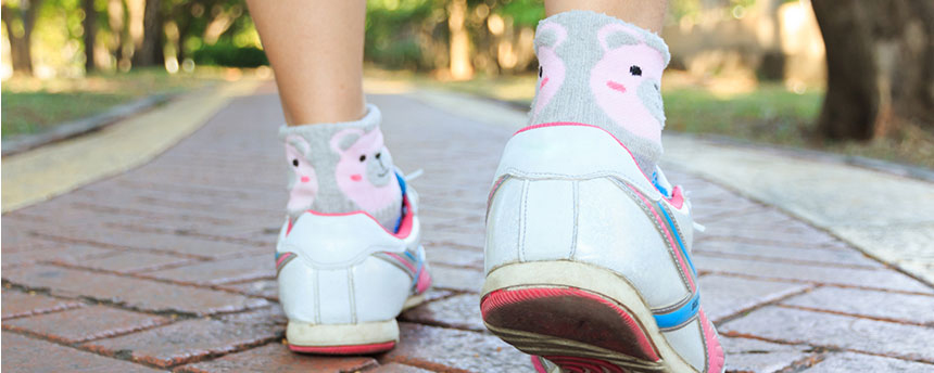 Woman's feet in running shoes take small step forward on brick walkway.