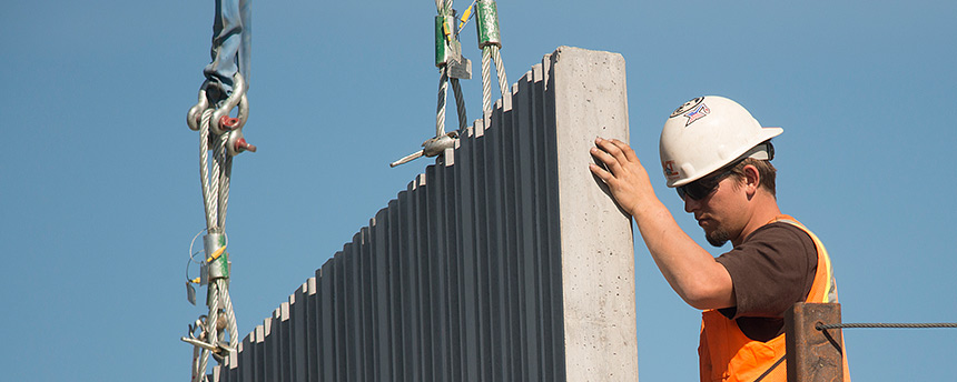 Man in hard hat helping adjust a steel wall on a construction site